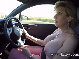 Mature nymph Sonia plays with her udders while driving
